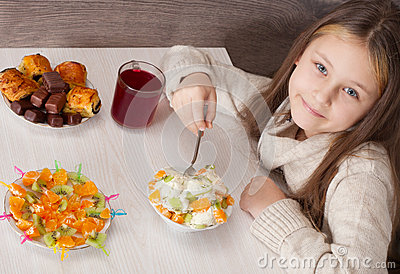 Beautiful little girl eating fruit