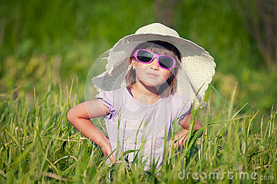 A beautiful little girl with a hat in a grain fiel