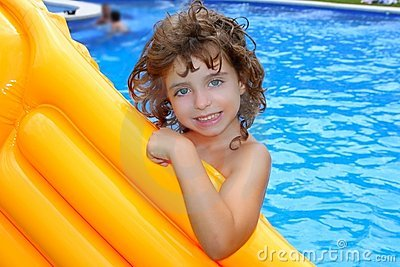 Beautiful little girl holding pool float smiling