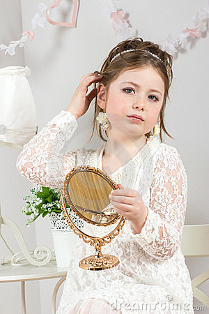 A beautiful little girl looking to small mirror