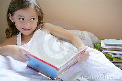 Beautiful little girl reading a book