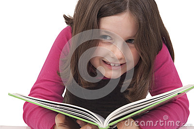 Beautiful little girl reading a book and smiling