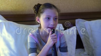 Beautiful Little Girl Sitting On The Bed In The Hotel And Watching TV. In The Hands Of A Girl Holding A Remote Control Stock Footage - Video of leisure, happiness: 90459898