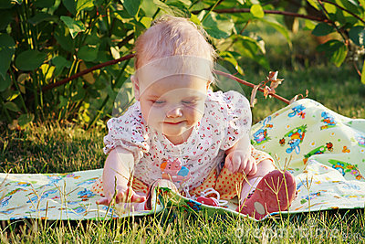 Beautiful little girl sitting on a evening meadow