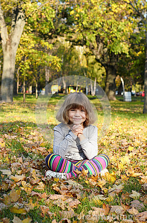 Beautiful little girl sitting in park
