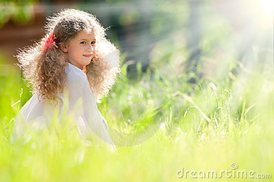 Beautiful little girl smiling and walking in field