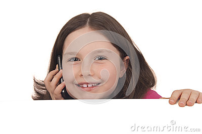 Beautiful little girl talking on a mobile phone behind copy spac