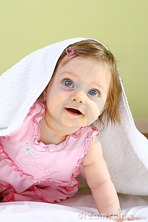 Beautiful little girl under white towel