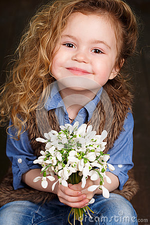 Free Beautiful Little Girl With A Big Bouquet Of Snowdrops. Royalty Free Stock Image - 51142896