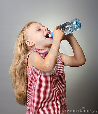 Free Beautiful Little Girl With Long Hair Drinking Water From Bottle On Gray Royalty Free Stock Image - 114833686