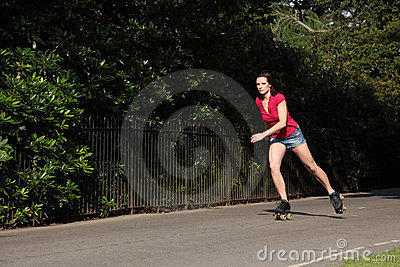 Beautiful long legged girl roller skating in park