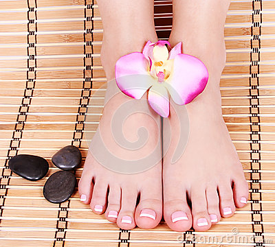 Beautiful manicured female bare feet with orchid flowers and spa stones over bamboo mat
