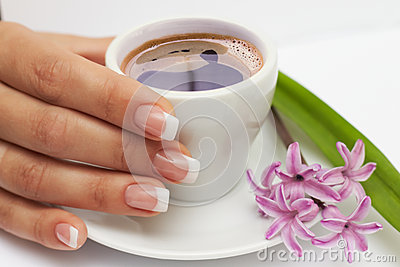 Beautiful manicured hand with french nails and cup of coffee and flowers at saucer