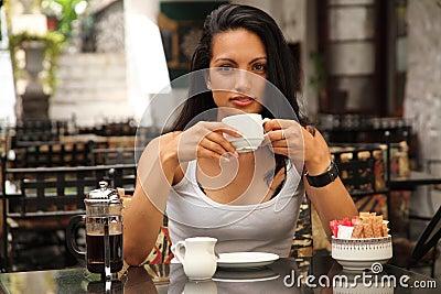 Beautiful mediterranean woman drinking coffee