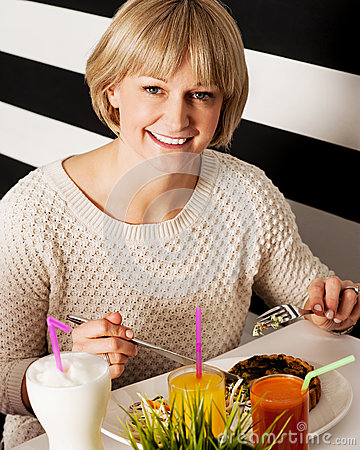 Beautiful middle aged lady enjoying her meal