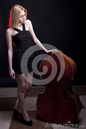 Beautiful model looking at a broken contrabass