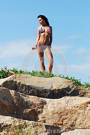 Beautiful model standing on top of rocks