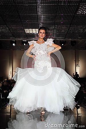 Beautiful model wear wedding dress walks catwalk Editorial Stock Photo