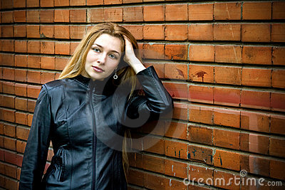 Beautiful modern woman in front of brick wall