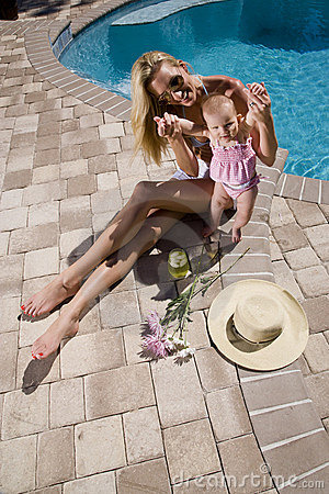 Beautiful mother and baby relaxing on pool deck