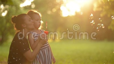 Beautiful mother with her daughter in nature making soap bubbles and laughing. Beautiful young mother together with her daughter in nature making soap bubbles