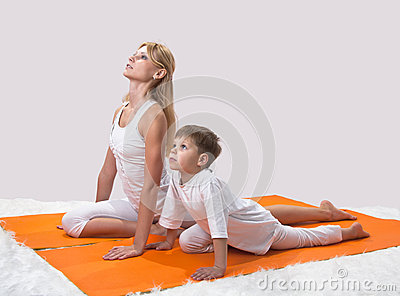 A beautiful  mother practices yoga with her son