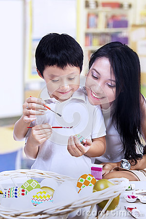 Beautiful mother teach son how to paint easter egg