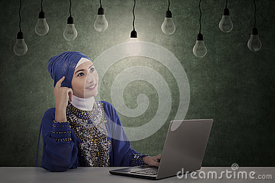 Beautiful muslim has idea under light bulbs