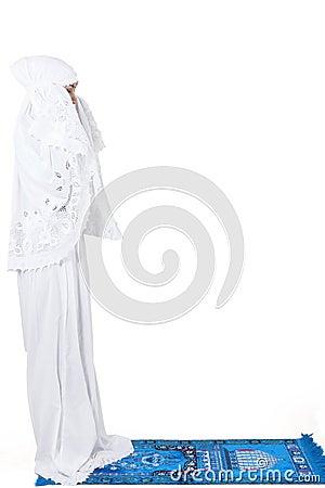 Beautiful muslim woman praying on carpet - isolated