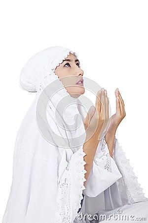 Beautiful muslim woman praying on white
