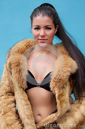 Beautiful naked woman in a fur coat
