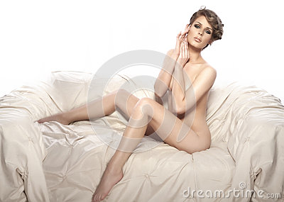 Beautiful naked woman sitting on the couch, isolated on white ba