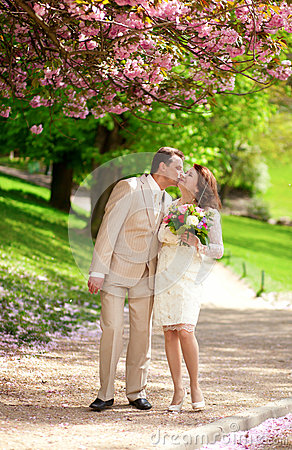 Beautiful newlywed couple kissing in park