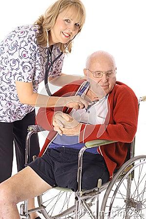 Beautiful nurse checking elderly patient