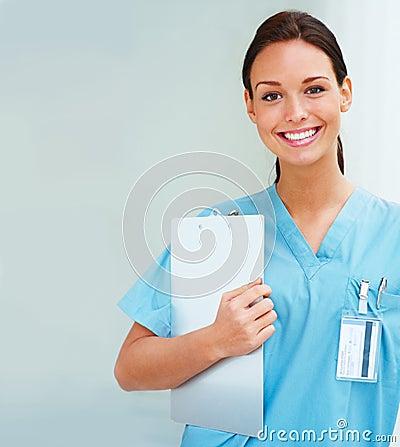 Beautiful nurse holding writingpad and smiling