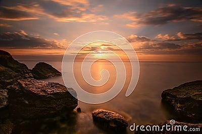 Beautiful ocean sunrise - calm sea and boulders stone coastline