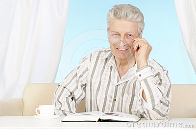 Beautiful old Caucasian man with book sits