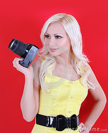 Beautiful photographer with the professional camera over red