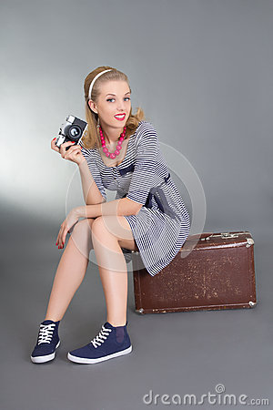 Beautiful pinup woman with camera sitting on brown retro suitcas