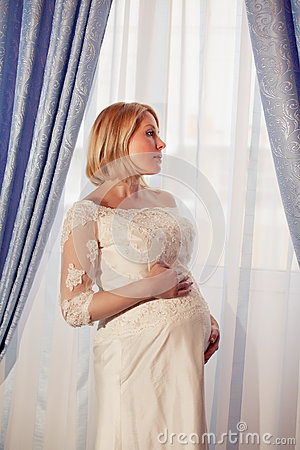 Beautiful pregnant bride posing against window