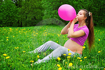 Beautiful pregnant woman blowing balloon