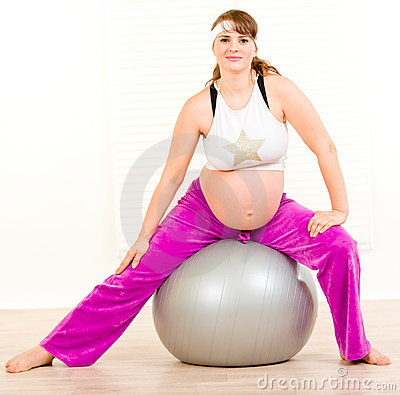 Beautiful pregnant woman doing exercises on ball
