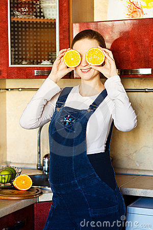 Beautiful pregnant woman at kitchen with orange