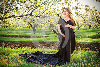 Beautiful pregnant woman in the lush spring garden in full for Gardening while pregnant
