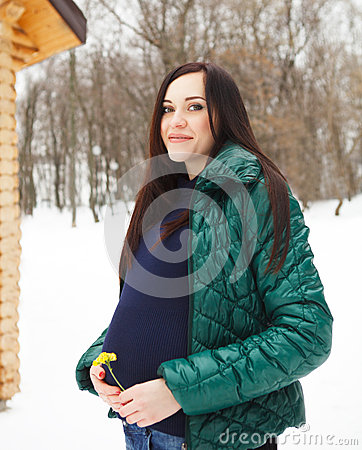 Beautiful pregnant woman in winter clothes outdoors
