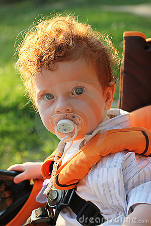 Beautiful red-haired boy in pram