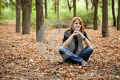 Beautiful red-haired girl in autumn park