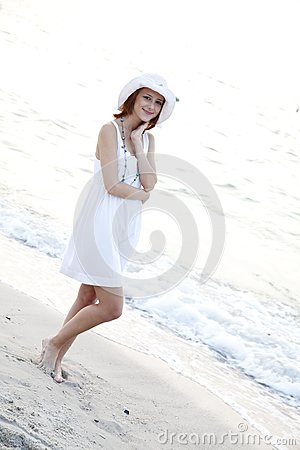 Beautiful red-haired girl in hat on the beach