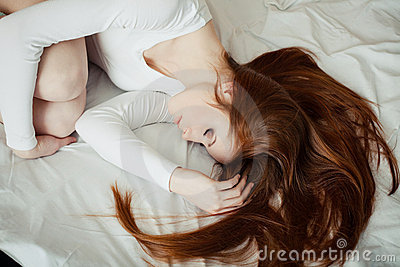 Beautiful red-haired girl sleep on the bed
