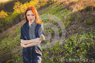 Beautiful red haired woman holding bouquet